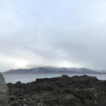 Dark lava stone in the front, pale blue sea in the middle, clouded mountain range in the back