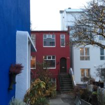 Part of a very blue house in front, and a lovely little red house set in the back