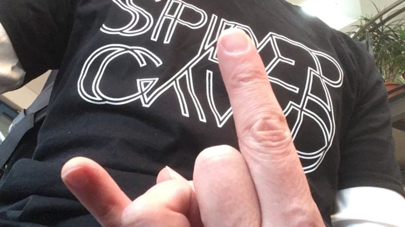 "Hand showing the ""rock"" two finger salute in front of the chest , wearing the Spidergawd logo T-Shirt"