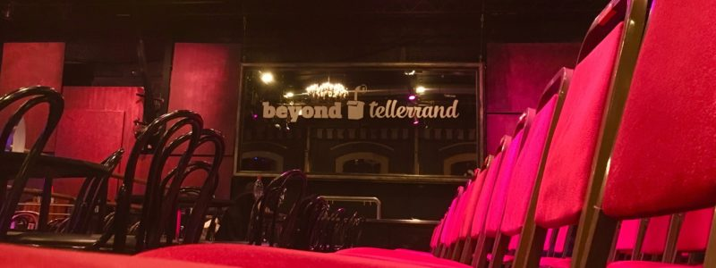 Empty row of red seats, in the background the Beyond Tellerrand Logo on a mirror above the bar