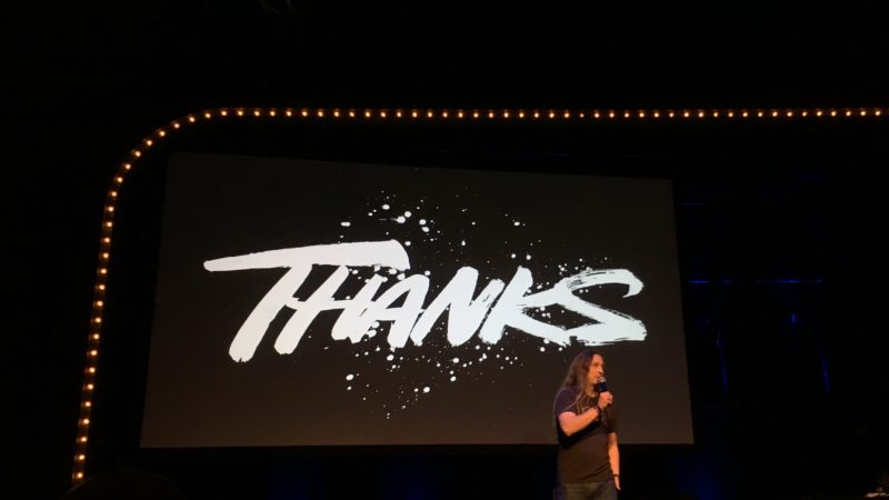 Slide above stage showing a hand lettered 'thanks'  with Marc in the foreground