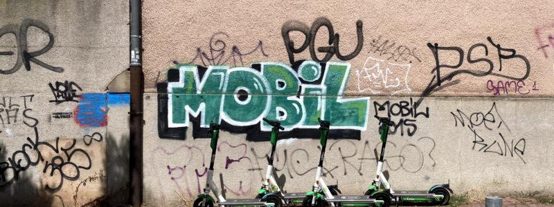 Vier Elektroscooter vor einen Grafitti Schriftzug Mobil
