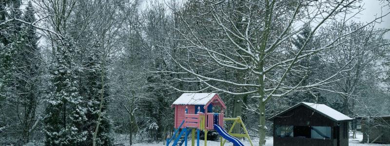 Bunte Kinderrutsche in einem verschneiten Garten