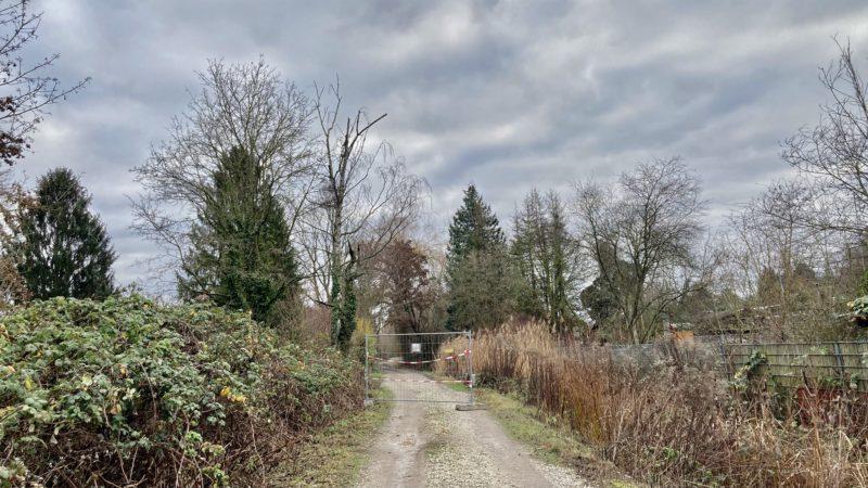 Bauzaun quer über den Weg mitten im Kleingartengebiet