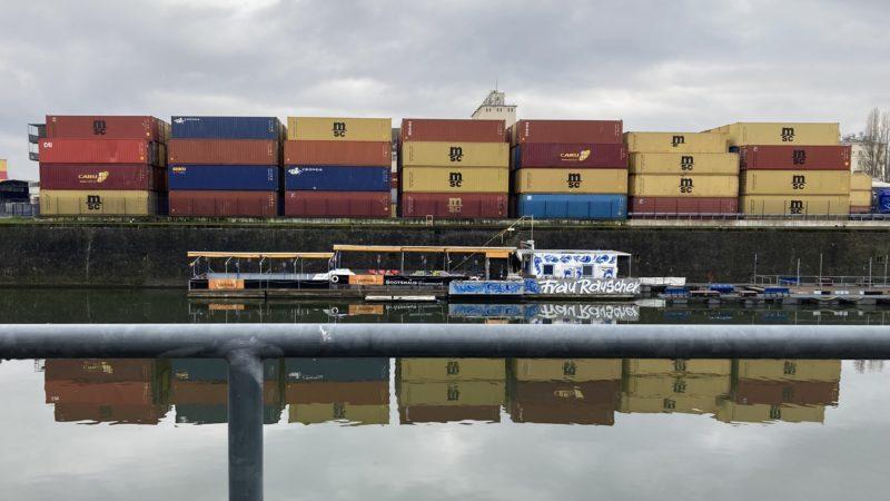 Blick über das Osthafenbecken auf bunte Frachtcontainer, davor ein Boot mit Frau Rauscher Schriftzug