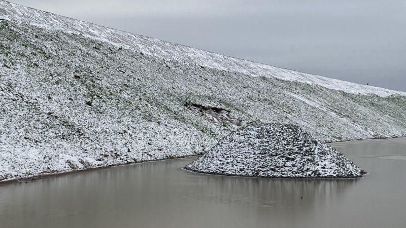 Verschneiter Abhang und Kieshaufen in einer Pfütze an der Autobahnbaustelle
